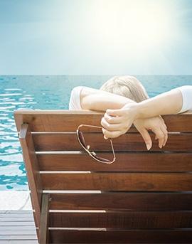 Aquadetente Luxembourg montre une femme qui se détend sur un banc en bois au soleil au bord de la mer.