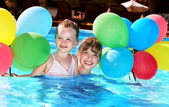Une mamam et son enfant dans une piscine avec plein de ballons fêtent les 10 ans d'Aqua Détente Luxembourg